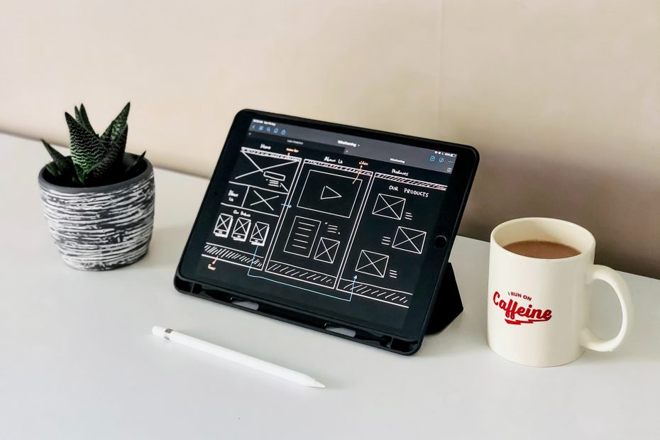 black ipad beside white ceramic mug on white table